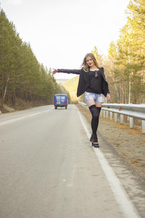 Beautiful young girl hitchhiking. In the United States and Canada stock image