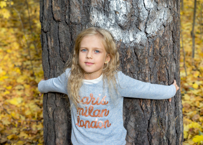 Beautiful young girl hugging tree royalty free stock photo