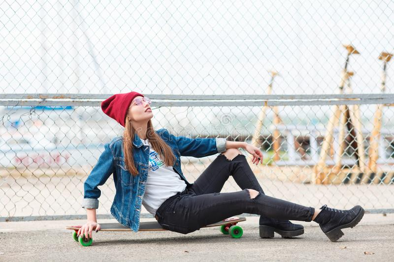 Pretty girl sitting on a skateboard outdoors on the nature background. stock image