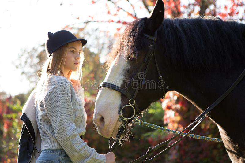 Beautiful young girl jockey talks with her horse dressing uniform competition royalty free stock image