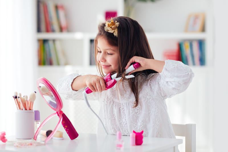 Beautiful young girl, kid curling the hair with iron curler and toy beauty set. Beautiful young girl, kid is curling the hair with iron curler and toy beauty set royalty free stock photo