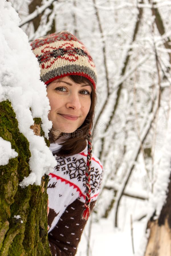 Beautiful young girl in knitted cozy wear looking out from behind tree in snowy forest. Portrait of smiling girl in winter park royalty free stock photos