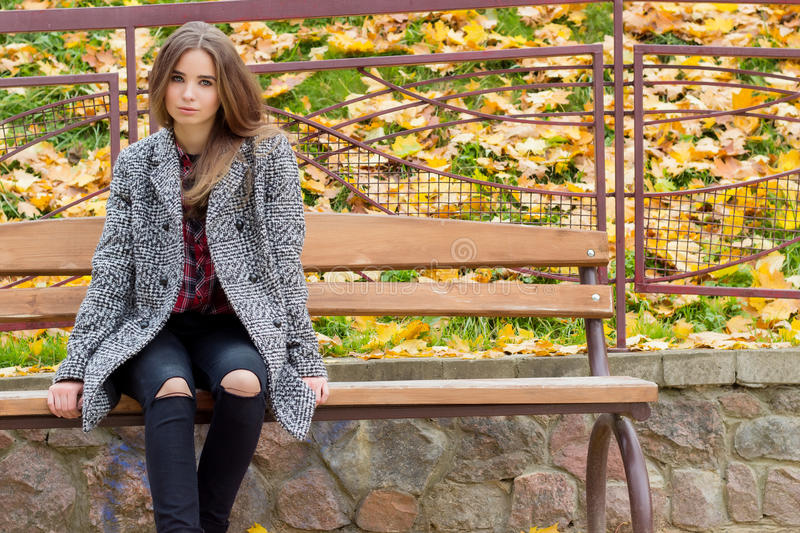 Beautiful young girl with large autumn sad eyes in a coat and ripped black jeans sitting on a bench in autumn park royalty free stock image