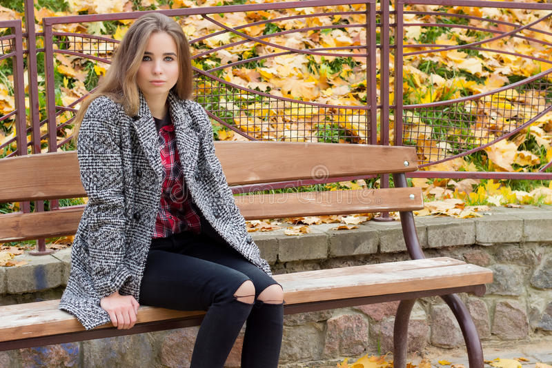 Beautiful young girl with large autumn sad eyes in a coat and ripped black jeans sitting on a bench in autumn park stock photography