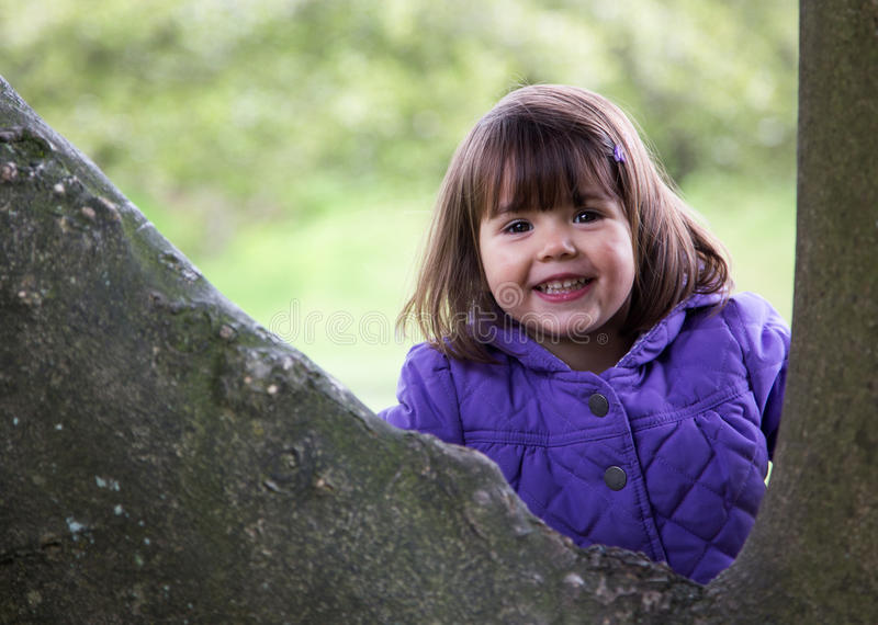 Beautiful Young Girl Laughing as She Enjoys Nature. Happy young girl laughs as she hides behind a tree royalty free stock photography