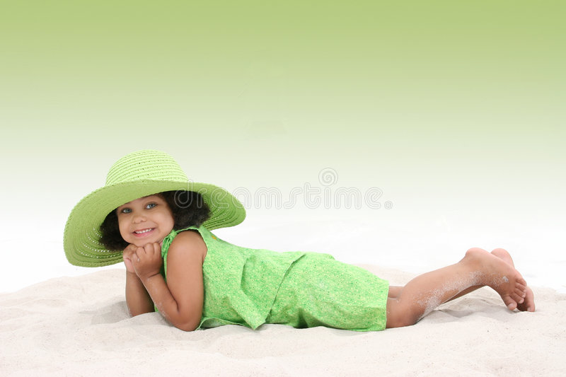 Beautiful Young Girl Laying In the Sand Wearing Big Green Hat stock images