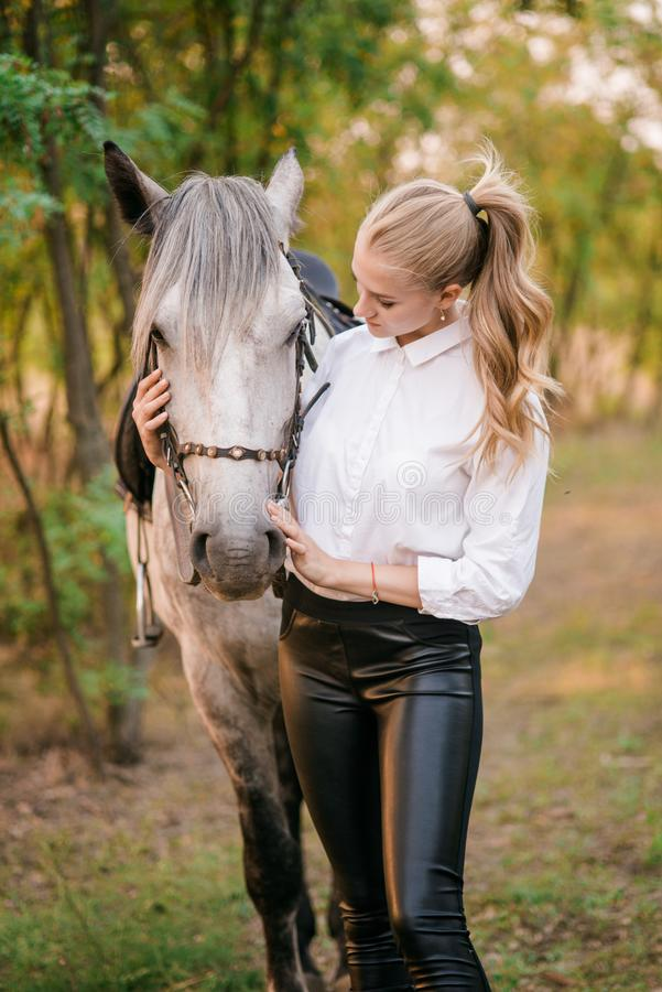 Beautiful young girl with light hair in uniform competition hugs her horse : outdoors portrait on sunny day on sunset. In autumn stock images