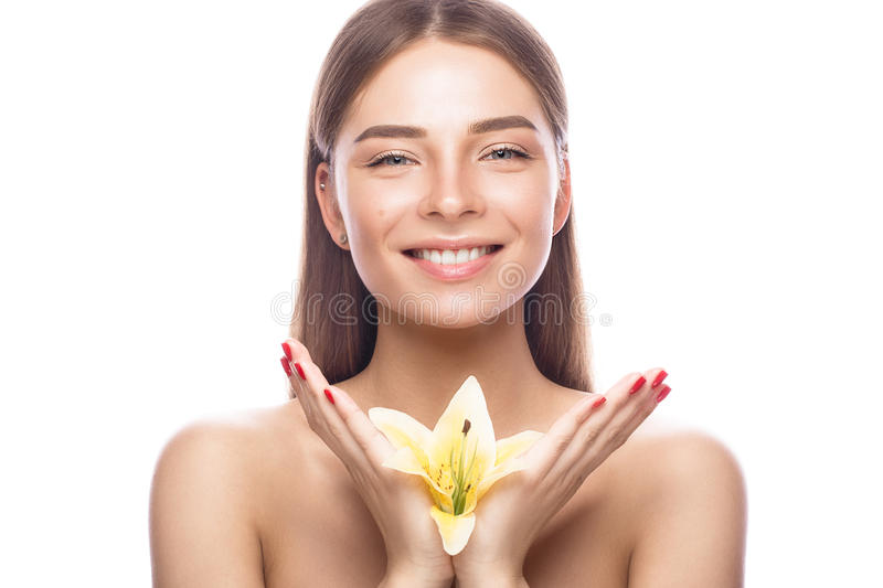 Beautiful young girl with a light natural make-up and perfect skin with flowers in her hand . Beauty face. stock photography