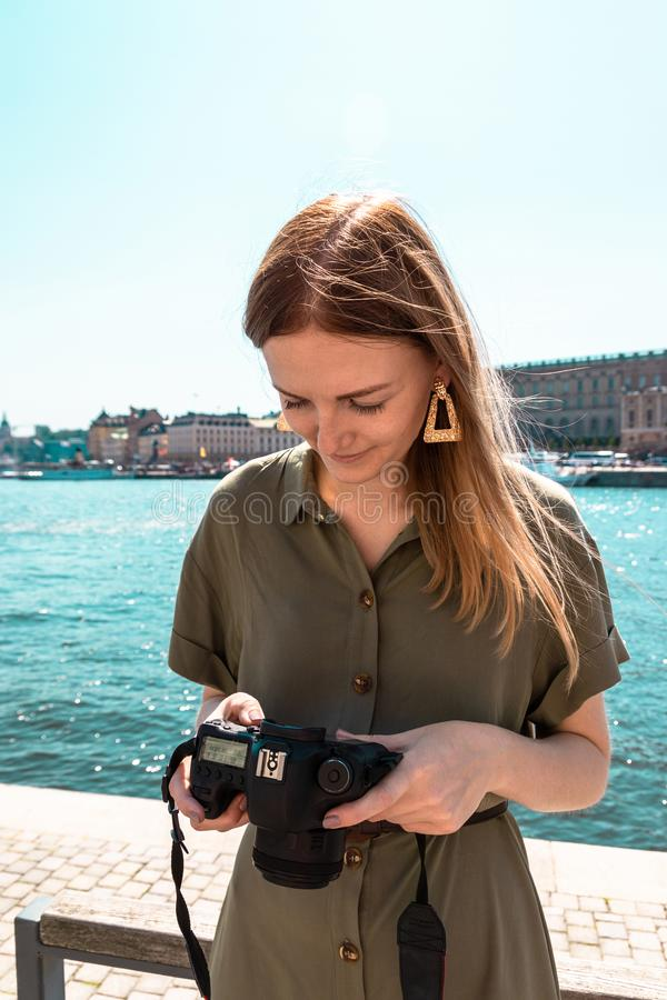 Beautiful young girl in a light summer dress of green khaki color holds a camera and looks at digital photos on the stock photography
