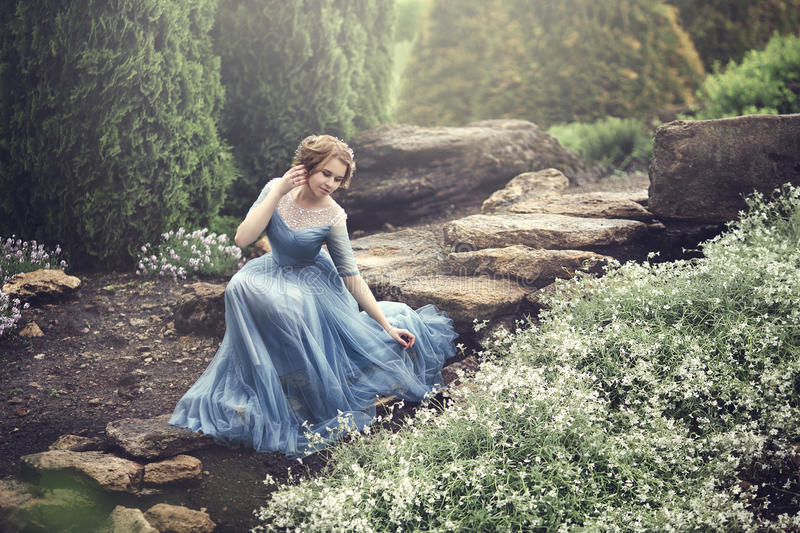 A beautiful young girl like Cinderella is walking in the garden. stock photography