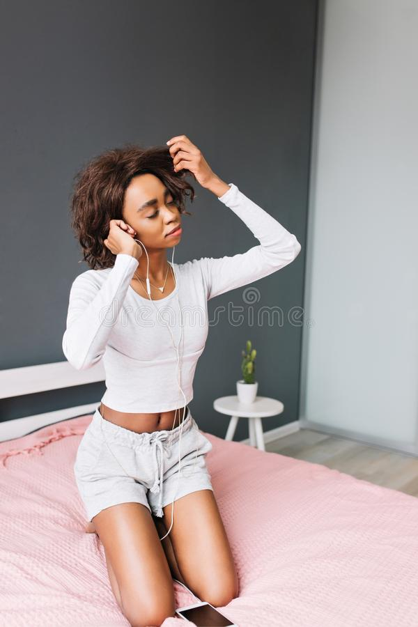 Beautiful young girl listening music in earphones on pink bed, touching her brown curly hair. Room with gray wall on royalty free stock image