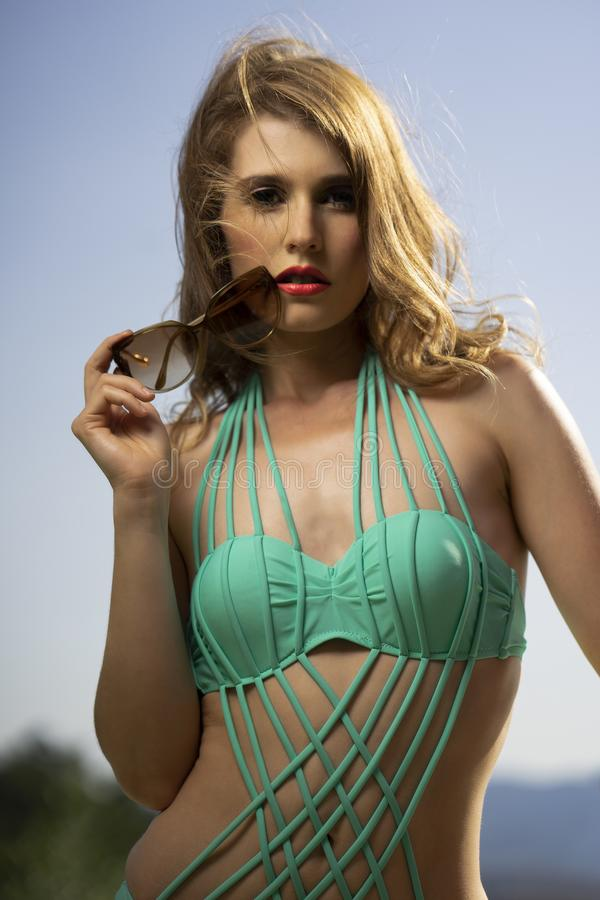Beautiful young girl with long blonde hair posing in green swims stock photography