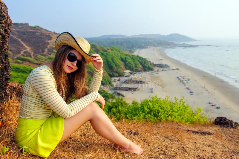 Beautiful young girl with long hair in straw hat, dark glasses and short yellow skirt sits on top against coastline and beach. In haze. Tourist woman sitting on stock image