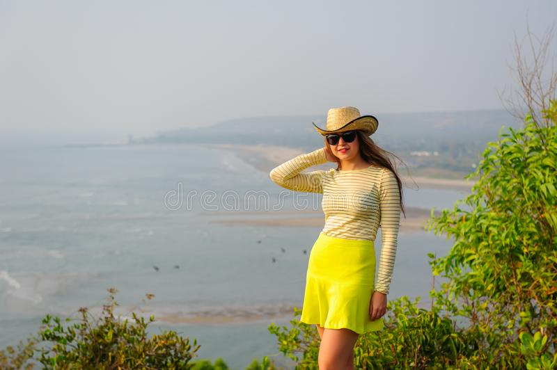 Beautiful young girl with long hair in straw hat, dark glasses and short yellow skirt stands on top against coastline and beach. In haze. Tourist woman stands stock photo