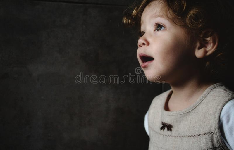 Beautiful young girl looking away against a dark moody background. Beautiful young girl looking away against a dark moody grungy background stock photos