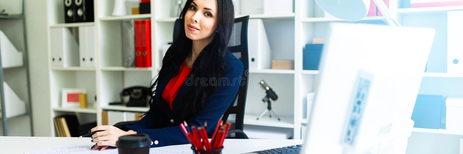 Beautiful young girl is looking through documents, sitting in the office at the table. royalty free stock photos