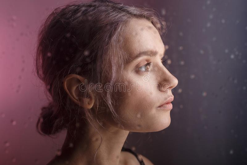 Beautiful young girl looks away on purple background. blurry drops of water run down the glass in front of her face. Beautiful young sensual thoughtful caucasian royalty free stock photo