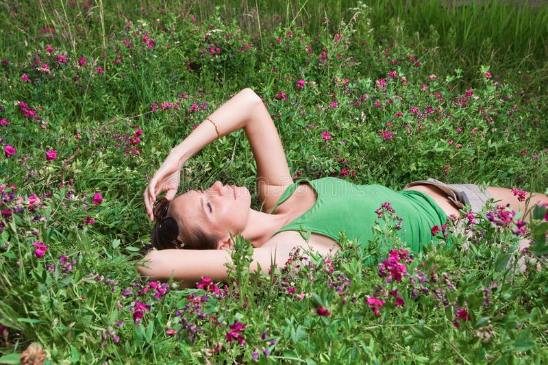 Beautiful young girl lying on green grass royalty free stock photo