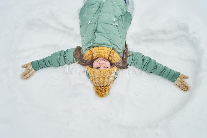 Beautiful young girl lying in the snow. making a snow angel royalty free stock photo