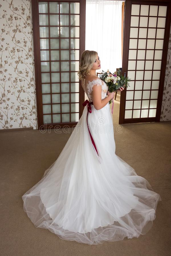 Beautiful young girl with make-up and hairdo stands in the lobby of the hotel in a wedding dress and with a wedding bouquet in her stock images