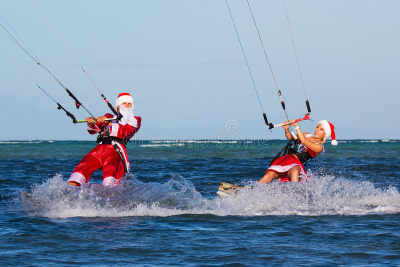 Beautiful young girl and man on the kites in the costume of Santa Claus. Christmas and New year on a tropical island. Extreme royalty free stock image