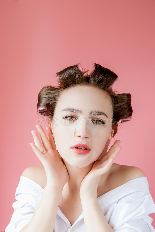 Beautiful young girl with a mask and curlers touching her face royalty free stock photos
