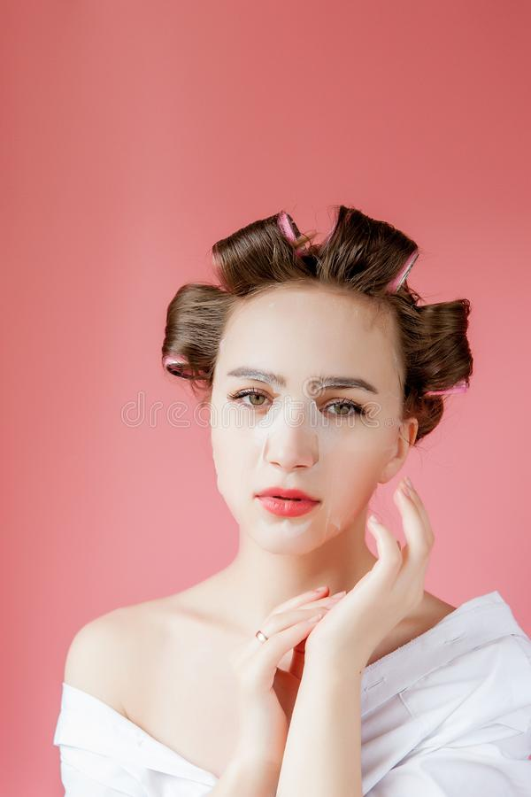 Beautiful young girl with a mask and curlers touching her face royalty free stock images