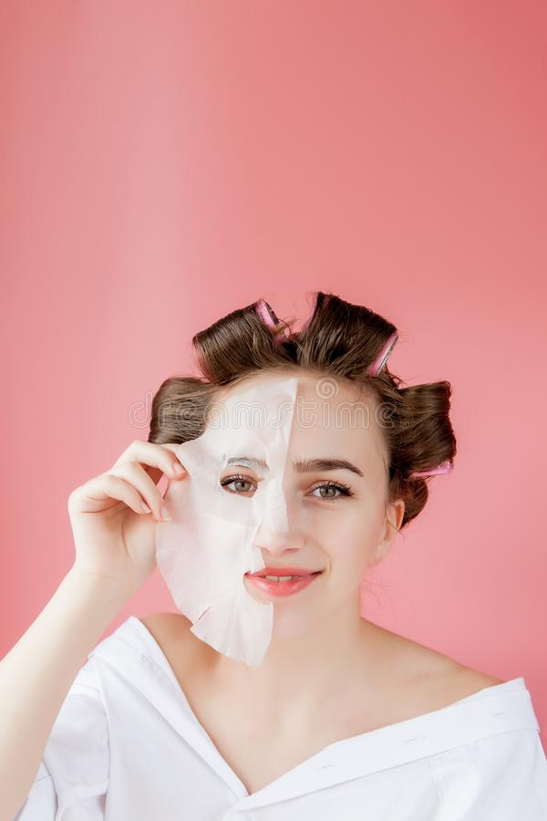 Beautiful young girl with a mask and curlers touching her face royalty free stock image