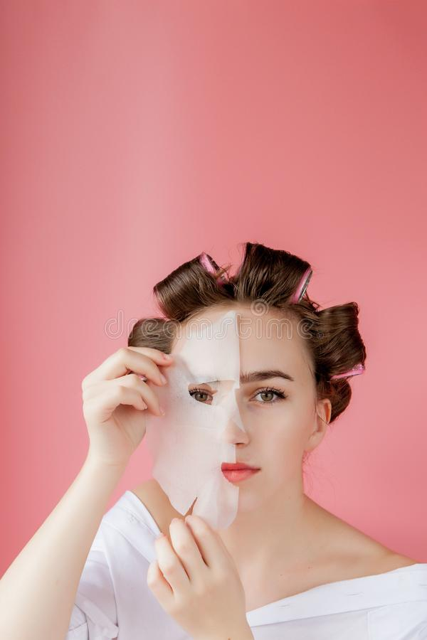 Beautiful young girl with a mask and curlers touching her face royalty free stock photography