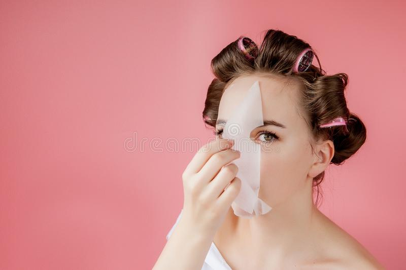 Beautiful young girl with a mask and curlers touching her face stock photography