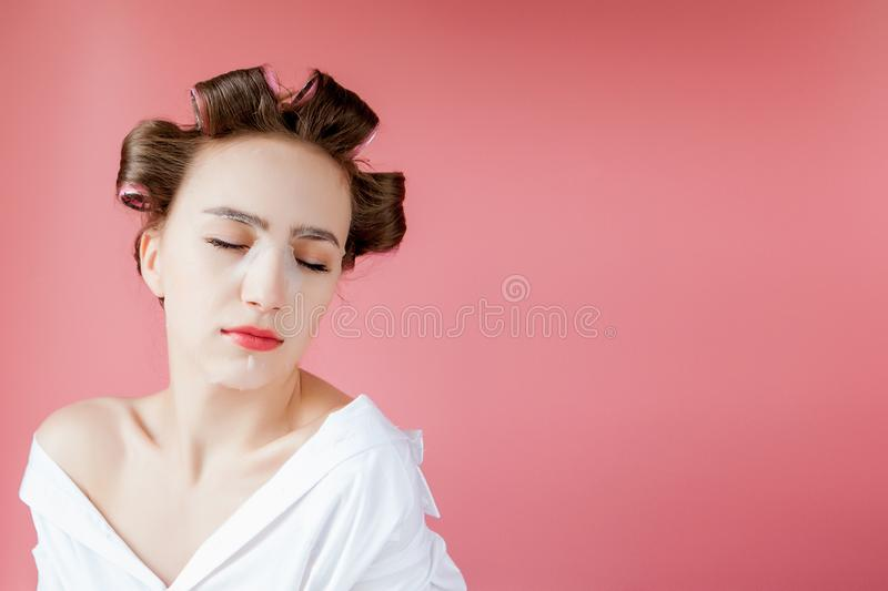 Beautiful young girl with a mask and curlers touching her face stock images