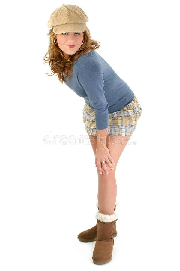 Beautiful Young Girl in Mini Skirt and Sweater. Beautiful young caucasian girl in plaid mini skirt, blue sweater, winter boots and cap. Shot over white stock photography