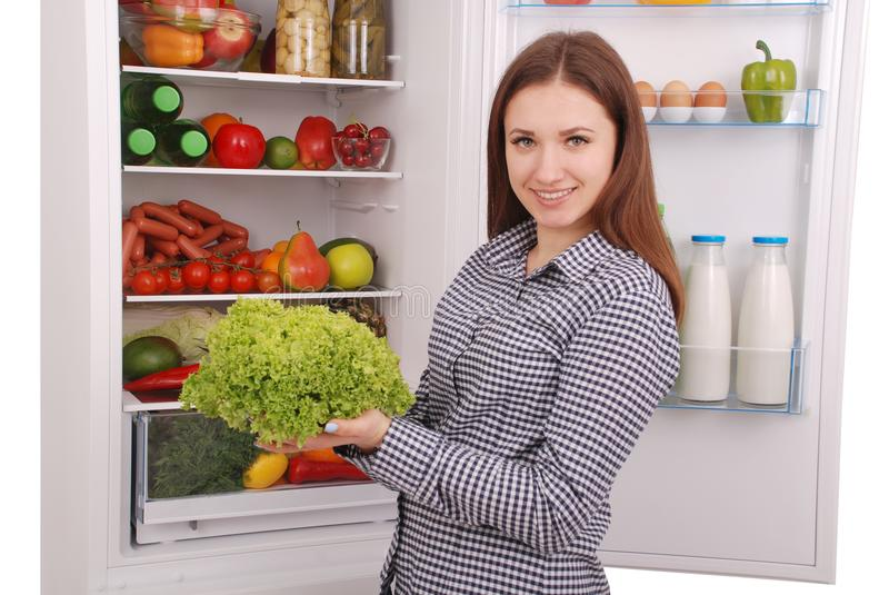 Beautiful young girl near the Fridge with healthy food. royalty free stock photos