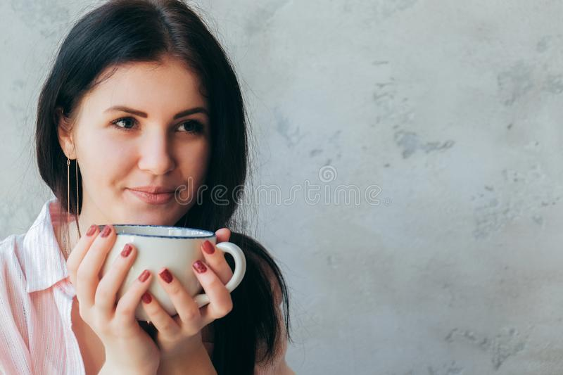 A beautiful young girl office worker holds in her hands and drinks coffee in a large cup. Student teenager is drinking tea stock image