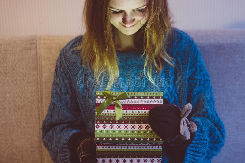 Beautiful and young girl opens a box with modern patterns in which a brightly burning gift. Light falls on her happy face royalty free stock images