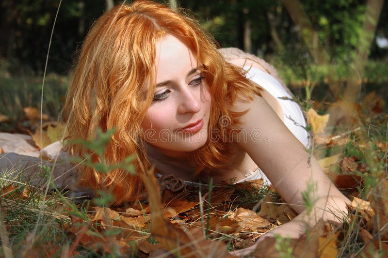 Beautiful young girl outdoors. Beautiful young girl lying on the ground royalty free stock photo
