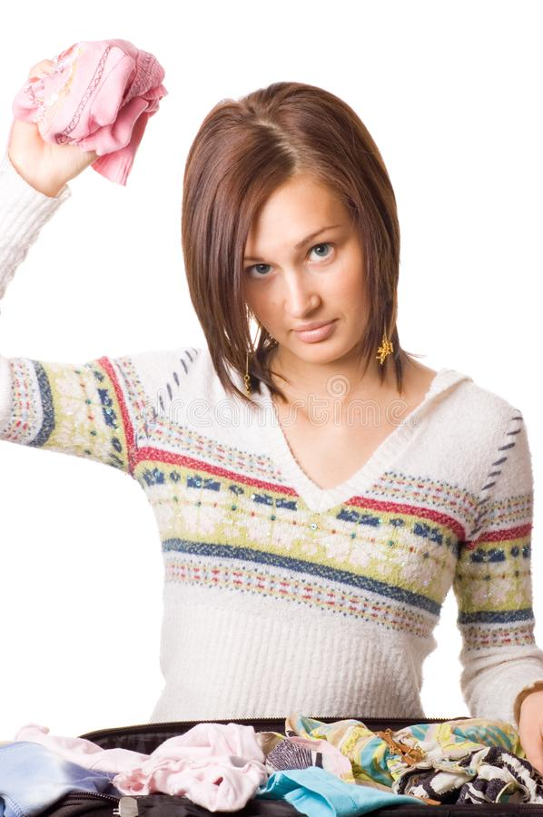 Beautiful young girl packs her clothes royalty free stock photo