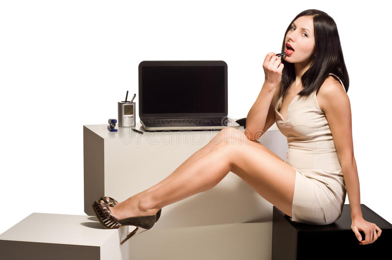 Beautiful young girl paints her lips with lipstick sitting at the computer in the office stock images