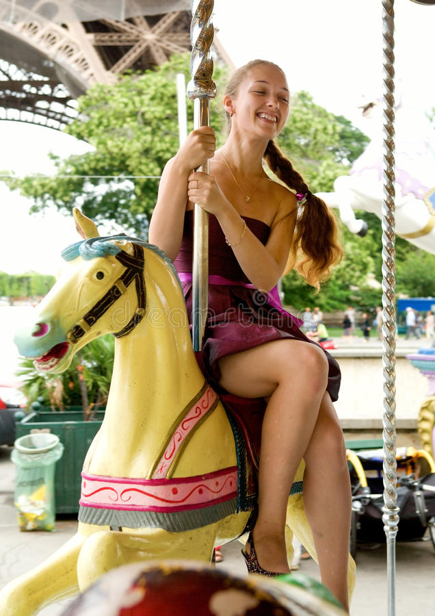 Beautiful young girl on Parisian marry-go-round royalty free stock images