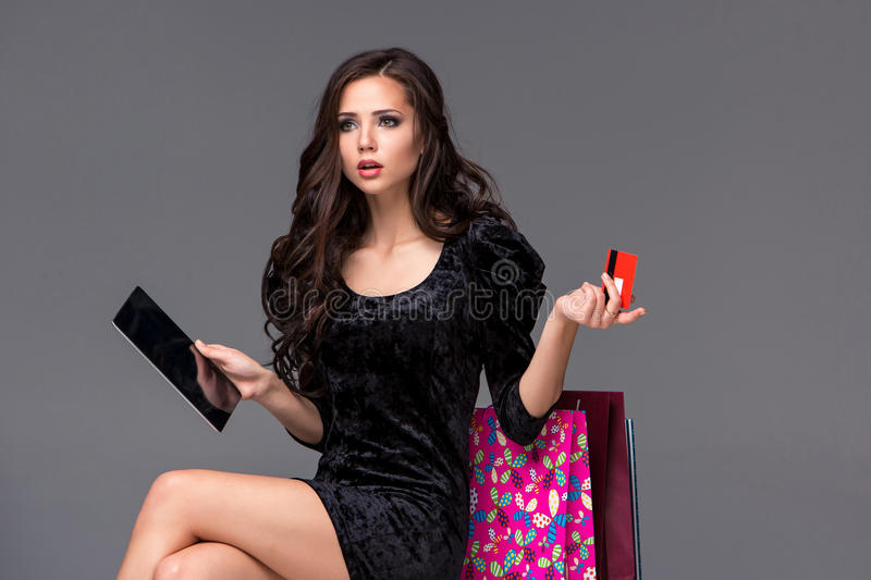 Beautiful young girl paying by credit card for. Shopping with a laptop and packages against gray background royalty free stock image