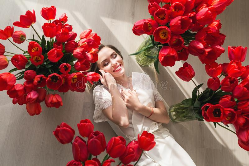 A beautiful young girl in a peignoir is lying on the floor between large bouquets of tulips. March 8 concept. royalty free stock image