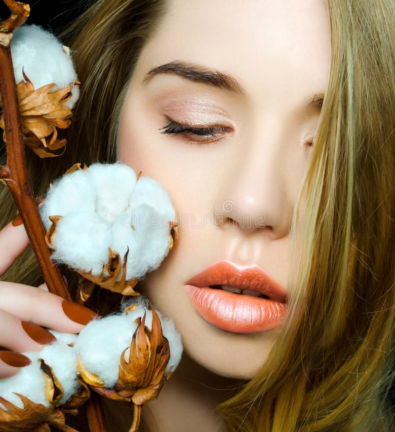 Beautiful young girl with perfect skin with nude make-up. Beauty portrait of a model with a branch of cotton in her royalty free stock images
