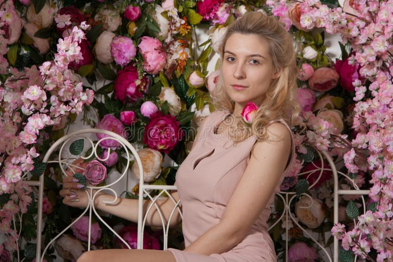 Beautiful young girl in a pink dress sitting on a white iron bench on a background of pink and white flowers royalty free stock photography