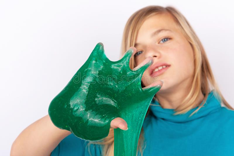 Beautiful young girl playing with green slime stock photos