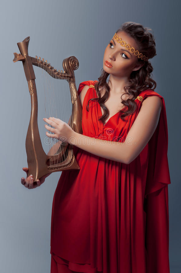 Beautiful young girl playing the harp stock images