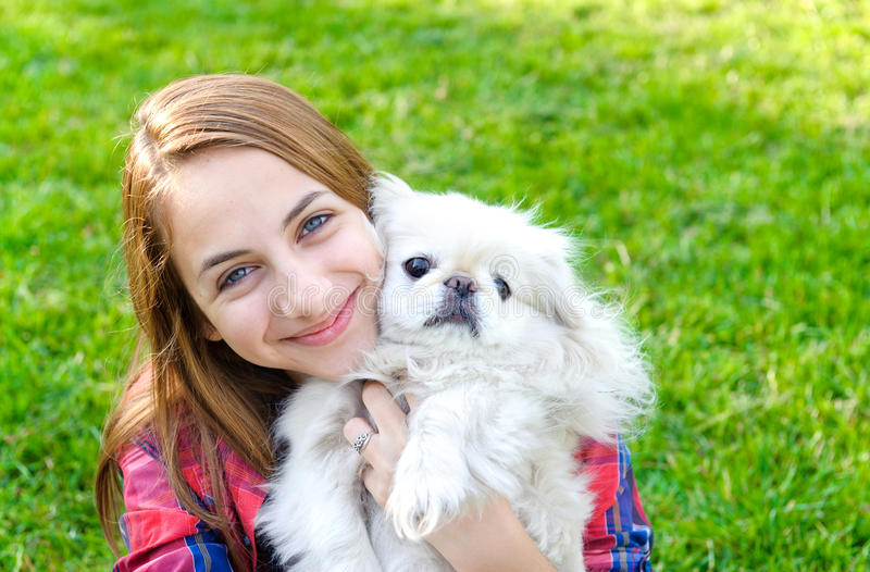 Beautiful young girl playing with her dog stock image