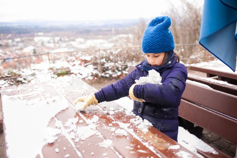 Beautiful young girl playing with snow. royalty free stock images