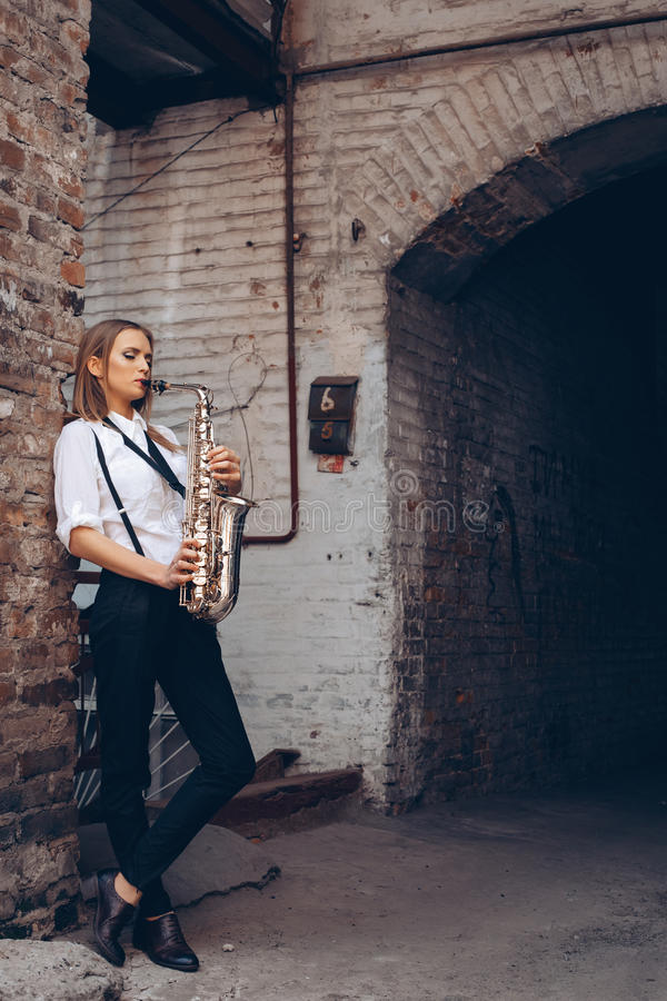 Beautiful young girl plays a saxophone standing near a white old wall - outdoors. Attractive woman in white shirt expression plays royalty free stock image