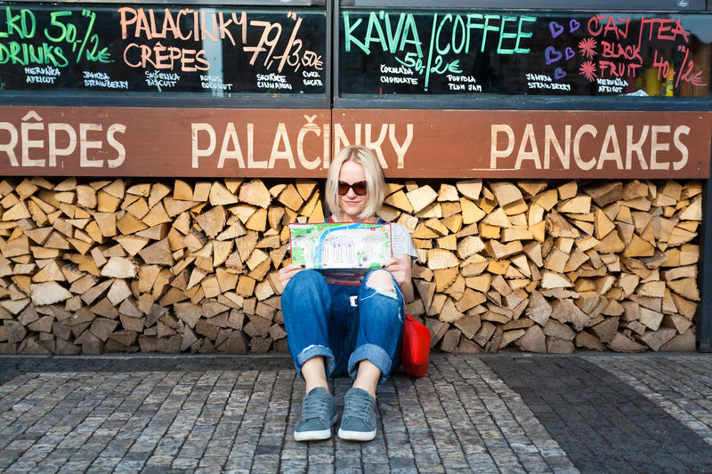 Beautiful young girl in Prague looks at the city map. PRAGUE, CZECH REPUBLIC - JUNE 05, 2016: Woman looks at map in the old town square. Tourism in Europe stock images