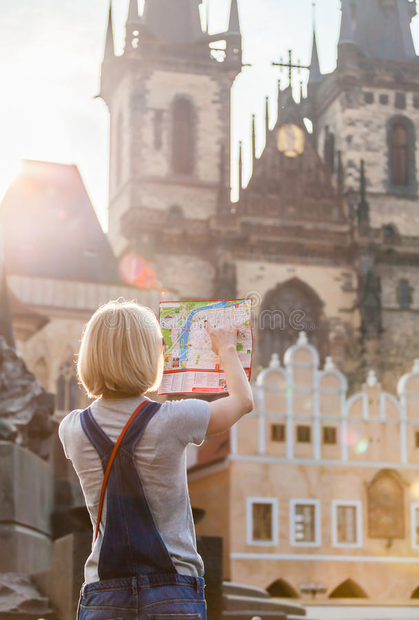 Beautiful young girl in Prague looks at the city map. PRAGUE, CZECH REPUBLIC - JUNE 05, 2016: Woman looks at map in the old town square. Travel guide, tourism stock photos